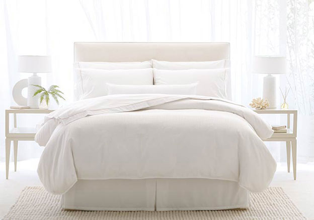 The all-white bed linen creates a halo effect in the room